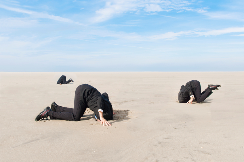 Three business people with their head in the sand